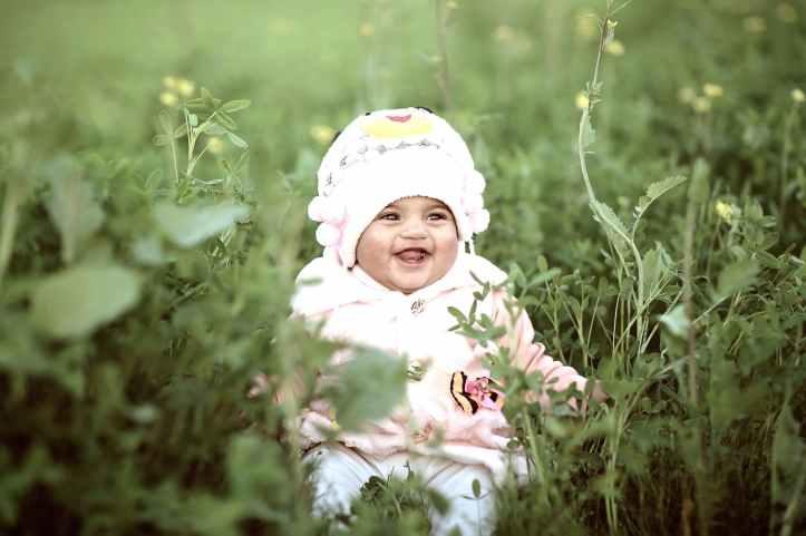 toddler wearing whit cap on green field